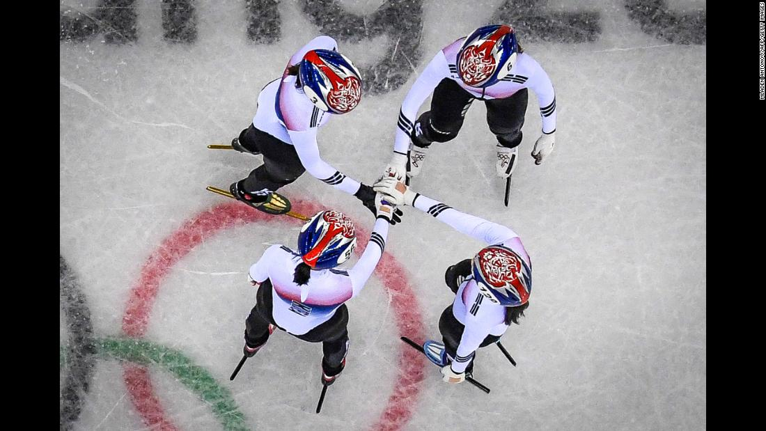 The South Korea women's 3,000-meter relay team holds hands before going on to win its short track speedskating heat.