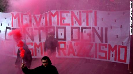 A man holds a flare in front of an anti-fascism banner during a protest Saturday in Macerata.