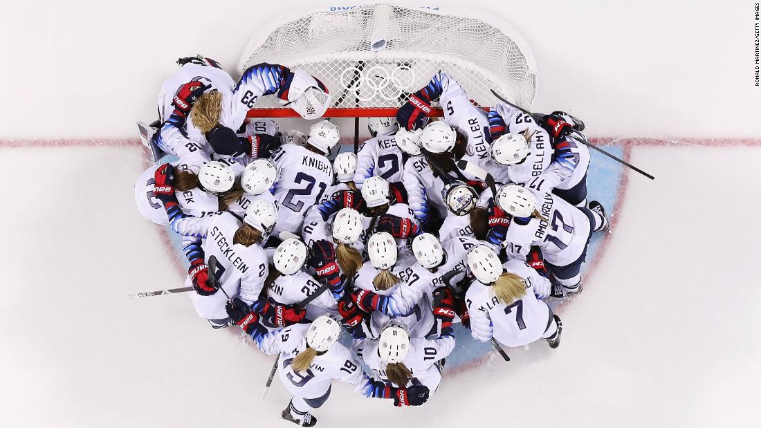 Team United States huddle at the goal before a women's ice hockey game against Finland.