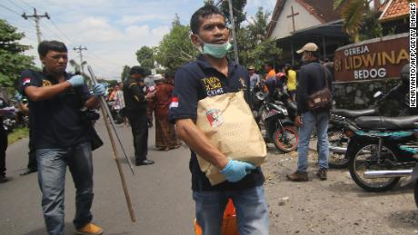 Indonesian police carry evidence after an attack at a church Sunday in Sleman, Yogyakarta province.
