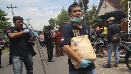 Indonesian police carry evidence after a knife attack at a church during a Sunday mass in Sleman, Yogyakarta province.