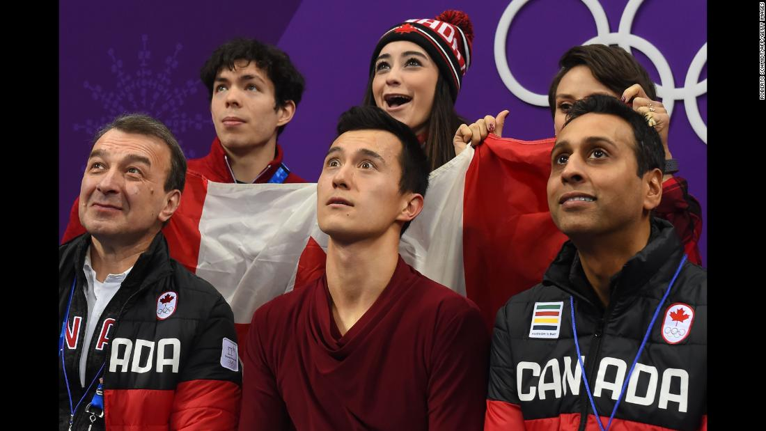 Canadian figure skater Patrick Chan, center front, reacts to his scores in the team competition.