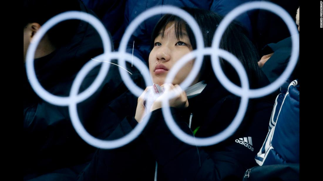 The Olympic rings are reflected by glass as a spectator watches a curling match.