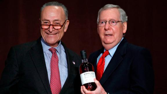 US Senate Minority Leader Chuck Schumer, a New York Democrat, at left, presents Senate Majority Leader Mitch McConnell, a Kentucky Republican, at right, with a bottle of bourbon at the University of Louisville's McConnell Center. (Bill Pugliano/Getty Images)