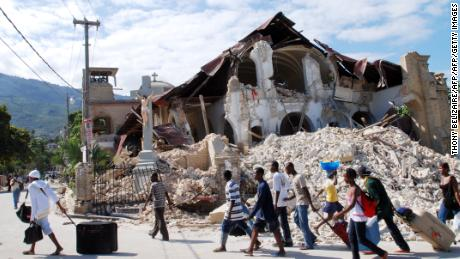 People walk by the collapsed Sacre Coeur Church in Port-au-Prince two days after the earthquake that devastated Haiti on January 12, 2010.