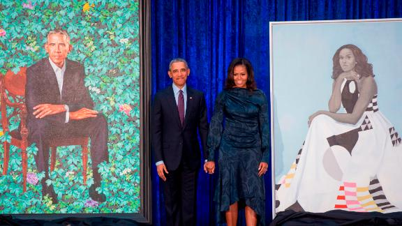 Former US President Barack Obama and First Lady Michelle Obama stand beside their portraits after their unveiling at the Smithsonian's National Portrait Gallery in Washington, DC, February 12, 2018. / AFP PHOTO / SAUL LOEB        (Photo credit should read SAUL LOEB/AFP/Getty Images)