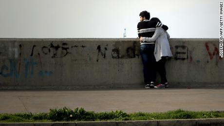 A Lebanese couple embrace as they stand on the seaside in Dbayeh north of Beirut, on February 7, 2014. AFP PHOTO/JOSEPH EID        (Photo credit should read JOSEPH EID/AFP/Getty Images)