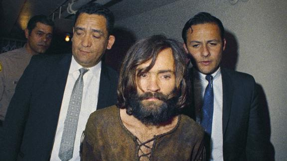 FILE - In this 1969 file photo, Charles Manson is escorted to his arraignment on conspiracy-murder charges in connection with the Sharon Tate murder case. The corpse of Manson will remain in a morgue for at least another month before would-be heirs can argue in court over who gets his remains. A Kern County Superior Court commissioner on Wednesday, Jan. 31, 2018, set a March 7 hearing in the dispute. (AP Photo, File)