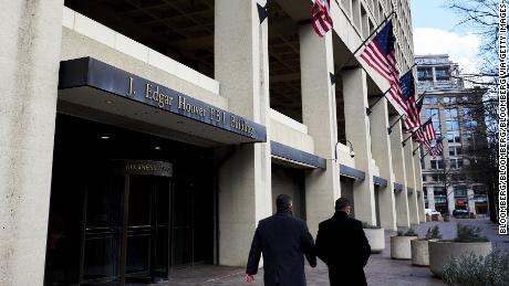 Pedestrians walk past the Federal Bureau of Investigation (FBI) headquarters in Washington, D.C., U.S., on Friday, Feb. 2, 2018. FBI and Justice Department officials got a warrant to spy on a Trump campaign associate by misleading a surveillance court judge, House Republicans contend in a newly released memo that Democrats have dismissed as a contrived account intended to protect the president. Photographer: T.J. Kirkpatrick/Bloomberg via Getty Images