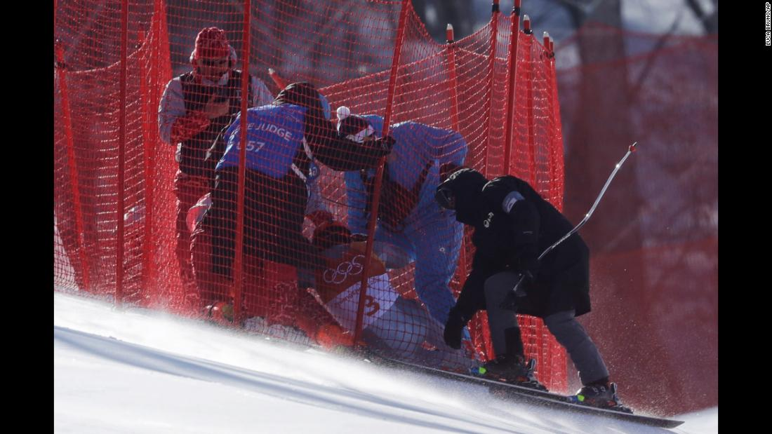 Officials assist Russian skier Pavel Trikhichev after he crashed in the downhill portion of the men's combined.