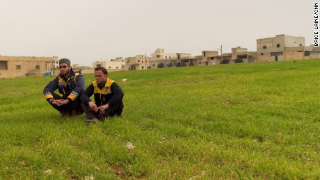 White Helmets volunteers Ayham Zeidan, 22, and Rami Dandal, 19, sit overlooking the scene of the attack in Saraqeb. Both were affected as they were trying to rescue other victims.