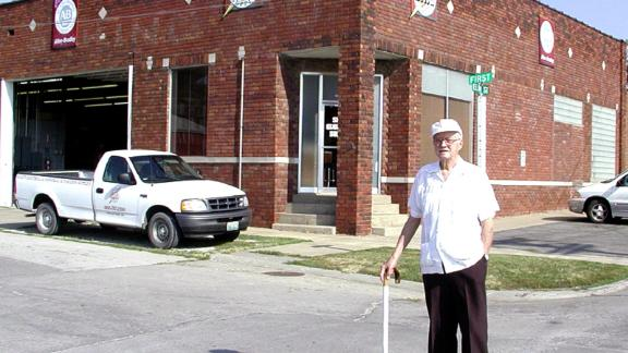 Richard Rohwedder  stands in front of the red brick building where his father's bread slicing machine was put into use in July 1928.