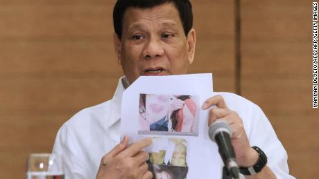 Philippine President Rodrigo Duterte shows a photo of an abused Filipina worker in Kuwait during a press conference in Davao City, February 9, 2018.