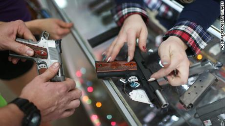 POMPANO BEACH, FL - DECEMBER 23: A customer compares handguns before buying one as a Christmas present at the National Armory gun store on December 23, 2015 in Pompano Beach, Florida. F.B.I. stats indicate that gun sales have increased dramatically this year, as reports indicate that firearms are a popular choice for a holiday present.