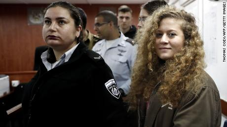 Palestinian teen protester Ahed Tamimi (R) stands for the beginning of her trial at Israel's Ofer Military Prison in the West Bank on February 13, 2018.