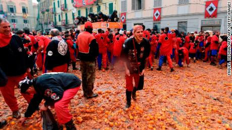 "Participants throw oranges from a float during the traditional ""Oranges battle"" of Ivrea Carnival, near Turin, on February 11, 2018.  Established in 1808, the Carnival of Ivrea is one of the oldest and most particular festivals in the world. It is the Battle of the Oranges that reevokes the civil war that broke out between the people of Ivrea and the Royal Napoleonic Troops. The battle is made up of squads of aranceri or orange throwers on foot (representing the people) and defending their piazzas from those throwing the oranges (that represent arrows) from carts (representing the Napoleonic troops).   / AFP PHOTO / MIGUEL MEDINA        (Photo credit should read MIGUEL MEDINA/AFP/Getty Images)"