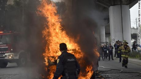 "Firefighters and police officers work in the scene of shoot-out in which eight allegedly drug traffickers were shot dead by Mexican Navy officers in Tlahuac, Mexico City, on July 20, 2017. According to authorities among those killed was ""Felipe de Jesus 'N'"" aka ""El ojos"" the leader of a Mexico City drug cartel. / AFP PHOTO / Pedro PARDO        (Photo credit should read PEDRO PARDO/AFP/Getty Images)"