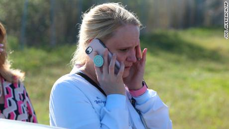A parent talks on cellphone waiting for news after a reports of a shooting at Marjory Stoneman Douglas High School in Parkland, Fla., on Wednesday, Feb. 14, 2018.