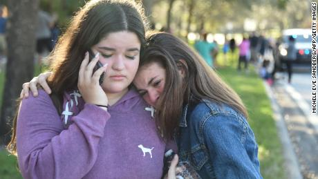 "Students react following a shooting at Marjory Stoneman Douglas High School in Parkland, Florida, a city about 50 miles (80 kilometers) north of Miami on February 14, 2018. A gunman opened fire at the Florida high school, an incident that officials said caused ""numerous fatalities"" and left terrified students huddled in their classrooms, texting friends and family for help. The Broward County Sheriff's Office said a suspect was in custody. / AFP PHOTO / Michele Eve Sandberg        (Photo credit should read MICHELE EVE SANDBERG/AFP/Getty Images)"