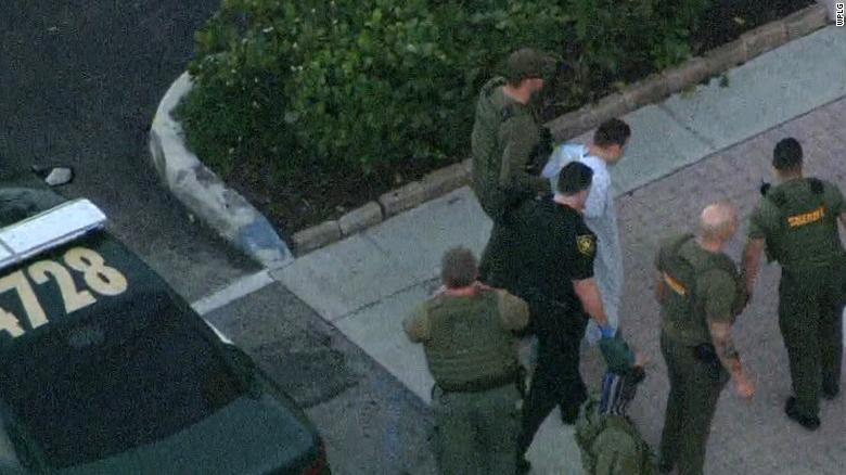 Law enforcement agents transport the suspect in Wednesday's school shooting.