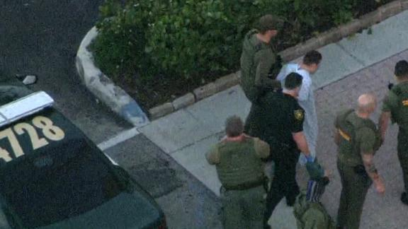 Law enforcement agents transport the suspect in Wednesday