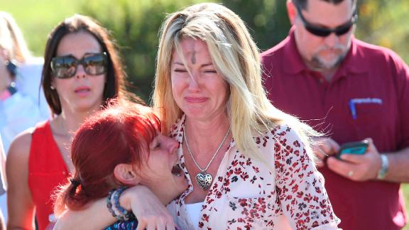 Parents wait for news after a shooting at Marjory Stoneman Douglas High School in Parkland, Florida, on Wednesday, February 14. At least 17 people were killed at the school, Broward County Sheriff Scott Israel said. The suspect, 19-year-old former student Nikolas Cruz, is in custody, the sheriff said. The sheriff said Cruz had been expelled for unspecified disciplinary reasons.