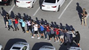 PARKLAND, FL - FEBRUARY 14:  People are brought out of the Marjory Stoneman Douglas High School after a shooting at the school that reportedly killed and injured multiple people on February 14, 2018 in Parkland, Florida. Numerous law enforcement officials continue to investigate the scene.  (Photo by Joe Raedle/Getty Images)