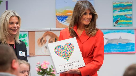 First lady Melania Trump holds up a gift as she exchanges valentines for Valentine's Day as she visits with children who are currently patients at the National Institutes of Health (NIH) at The Children's Inn at NIH in Bethesda, Maryland.