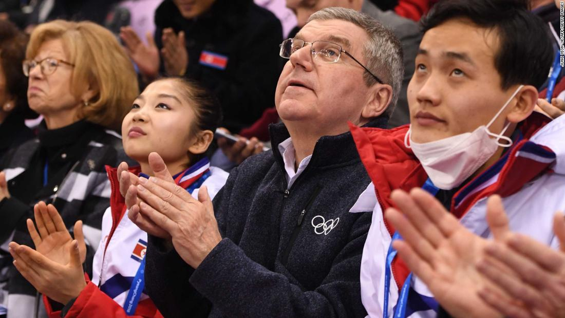Thomas Bach, president of the International Olympic Committee, sits between the North Korean figure skating duo of Ryom Tae Ok and Kim Ju Sik.