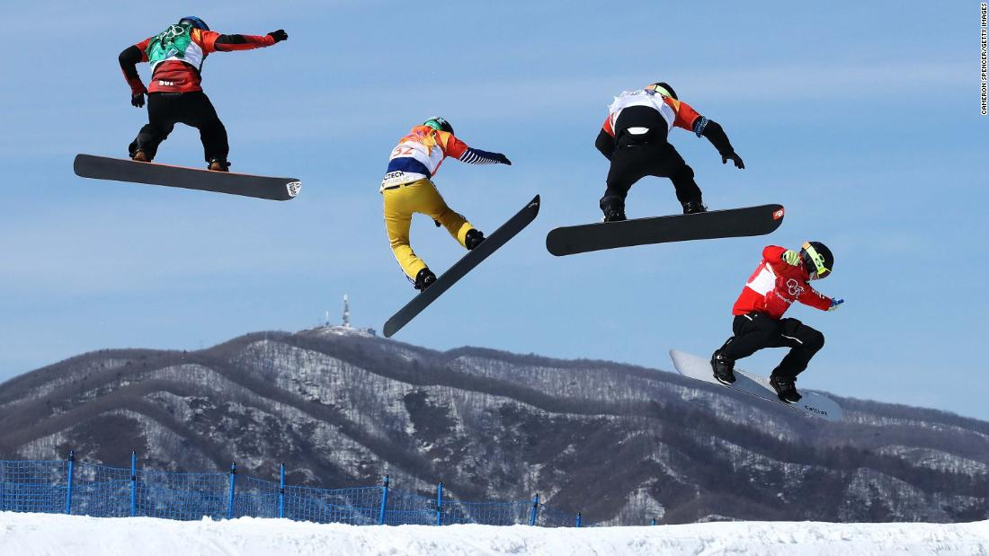 Athletes race in a snowboard cross quarterfinal.