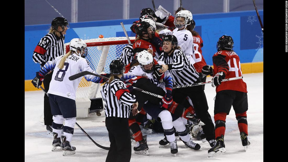 An official tries to separate players from Canada and the United States during a preliminary round hockey game. Canada won 2-1.