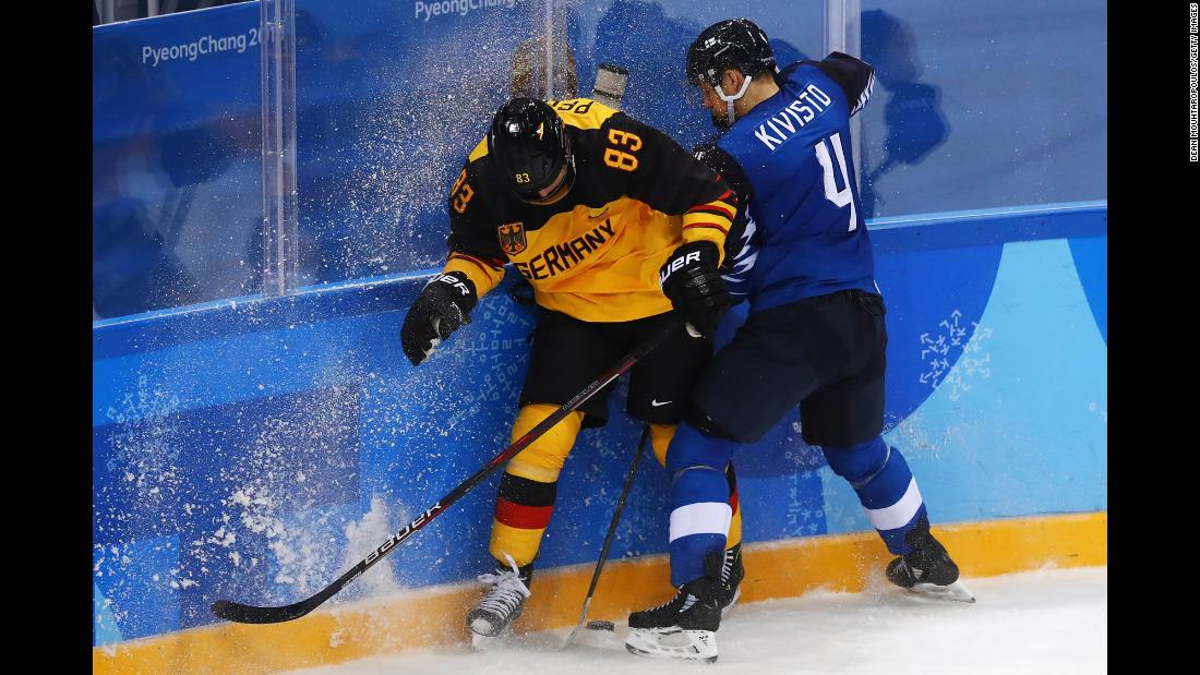 Germany's Leonhard Pfoderl, left, and Finland's Tommi Kivisto battle for the puck during a preliminary round game.