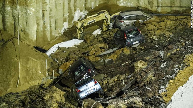 Workers remove cars that were sucked down into the sinkhole.