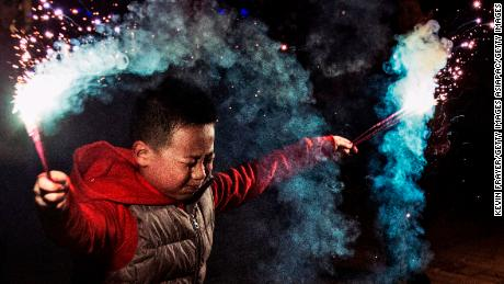 A boy uses sparklers to celebrate Chinese Lunar New in Beijing, China (2005). In China, fireworks were traditionally used to ward off evil spirits.