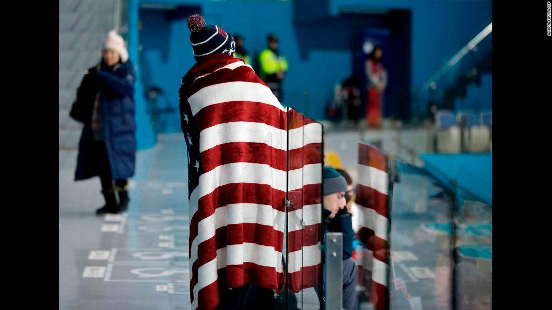 A spectator draped with an American flag watches a men's curling match.
