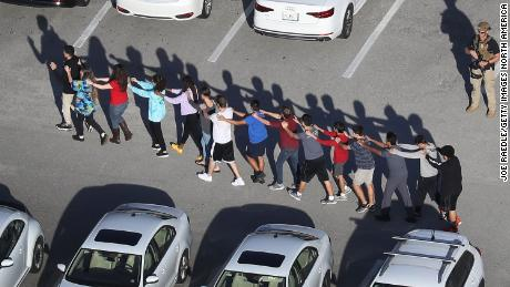PARKLAND, FL - FEBRUARY 14:  People are brought out of the Marjory Stoneman Douglas High School after a shooting at the school that reportedly killed and injured multiple people on February 14, 2018 in Parkland, Florida. Numerous law enforcement officials continue to investigate the scene.  (Photo by Joe Raedle/Getty Images) *** BESTPIX ***