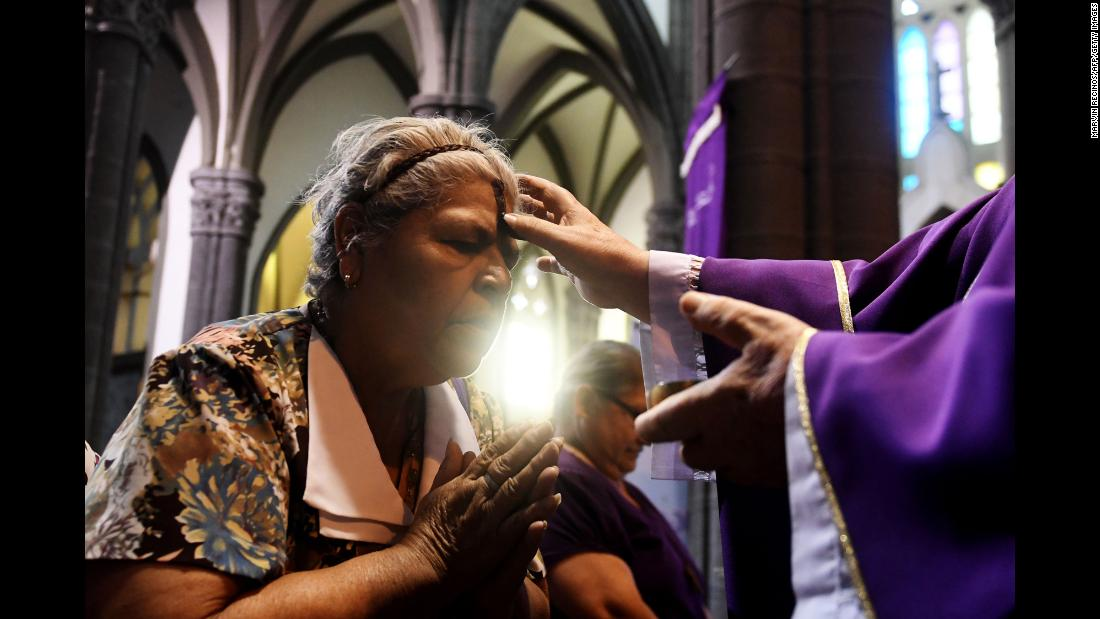 A Catholic faithful has her forehead marked during Ash Wednesday in San Salvador, El Salvador, on Wednesday, February 14. Ash Wednesday marks the beginning of the Christian period of Lent, prior to Holy Week.