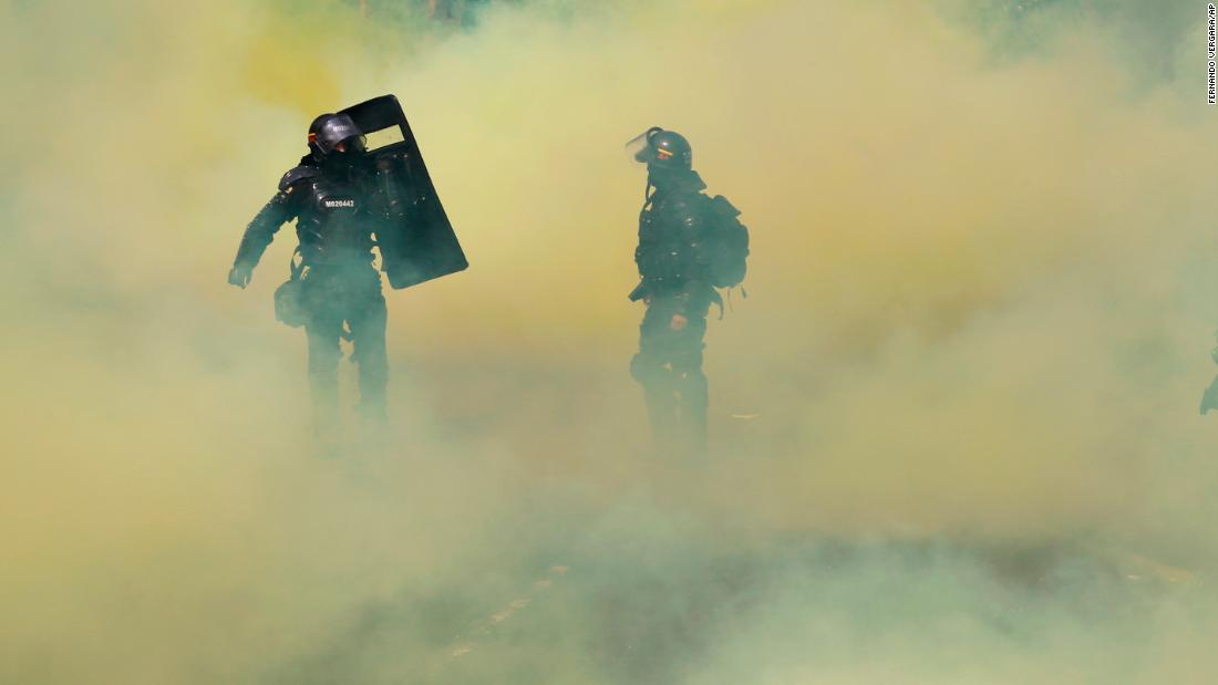 Riot police walk amid a cloud caused by smoke grenades launched by security forces to disperse protesters blocking bus lanes in Bogota, Colombia, on Wednesday, February 14. Protesters were demanding improvements to public transportation.