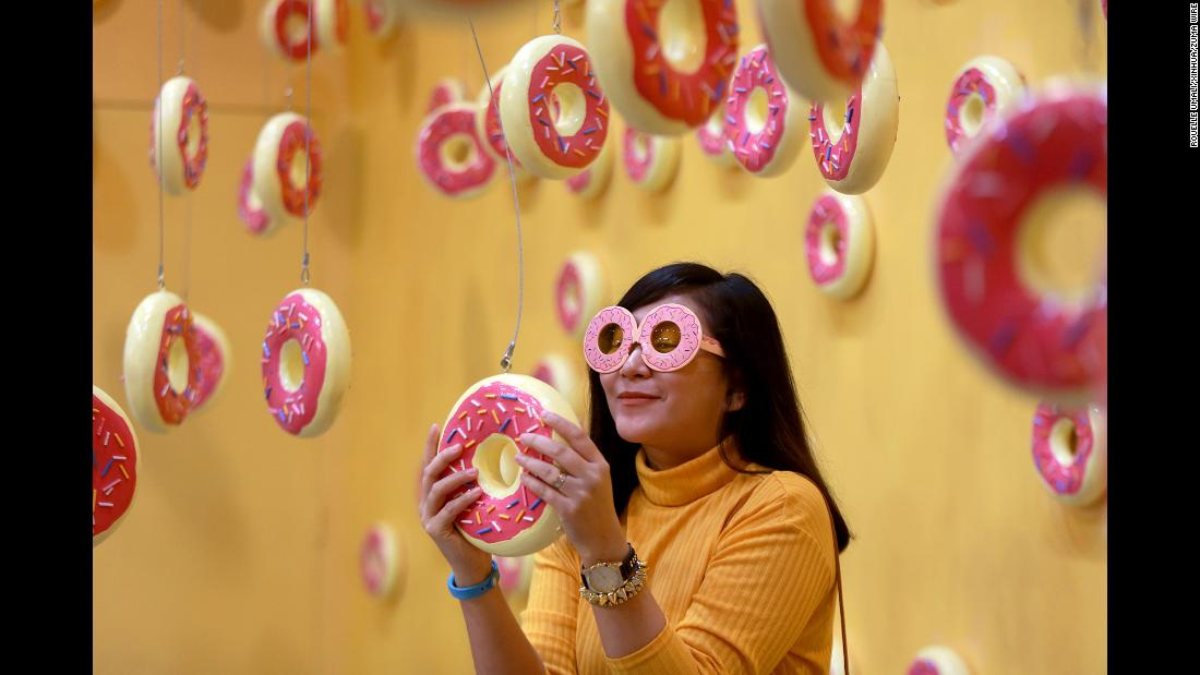 A woman holds a doughnut installation inside a room at the Dessert Museum in Pasay City, the Philippines, on Sunday, February 11.