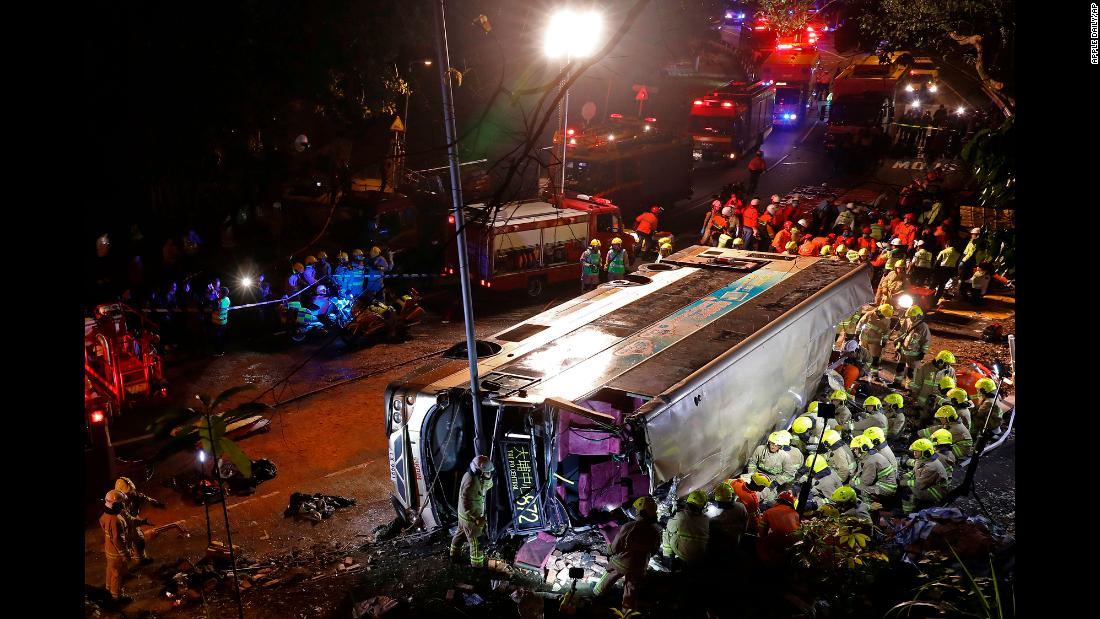 "Firefighters hurry to try to remove injured passengers from a double-decker bus lying on its side in Hong Kong, on Saturday, February 10. <a href=""https://www.cnn.com/2018/02/10/asia/hong-kong-deadly-bus-crash/index.html"" target=""_blank"">The crash killed 19 people</a> and injured dozens more, authorities in the southern Chinese city said."
