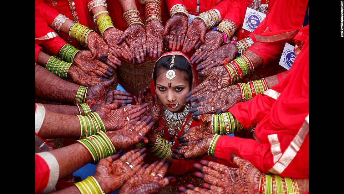 Brides display their hands decorated with henna around a bride as she poses for her own photographer during a mass marriage ceremony in Ahmedabad, India, on Sunday, February 11.