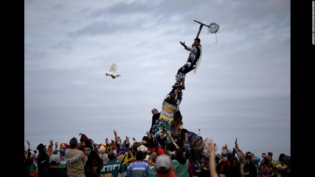 "A reveler releases a chicken from a cage after climbing a greased pole during the Faquetaique Courir de Mardi Gras celebration in Eunice, Louisiana, on Tuesday, February 13. <a href=""https://www.cnn.com/travel/article/mardi-gras-beads-throws-trnd/index.html"" target=""_blank"">Interesting Mardi Gras throws</a>"