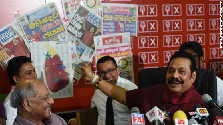 Former Sri Lankan president Mahinda Rajapakse holds a newspaper displaying areas where his party won local government seats during a press conference in Colombo on February 12, 2018.