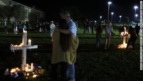 PARKLAND, FL - FEBRUARY 15:  Students, friends, and family members gather around candlit crosses during vigil for victims of the mass shooting at Marjory Stoneman Douglas High School yesterday, at Pine Trail Park, on February 15, 2018 in Parkland, Florida. Yesterday Police arrested 19 year old former student Nikolas Cruz for killing 17 people at the high school.  (Photo by Mark Wilson/Getty Images)