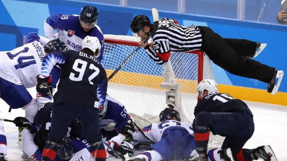 A referee jumps onto the net to avoid play during the hockey game between Slovakia and the United States.