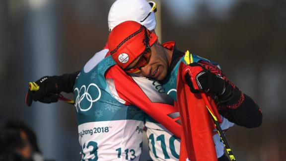 Tonga's Pita Taufatofua, right, hugs Morocco's Samir Azzimani after finishing the 15-kilometer freestyle. Taufatofua is most known for going shirtless during the last two opening ceremonies. He competed in taekwondo at the Rio Summer Games in 2016.