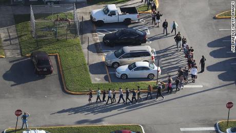 Students leave Marjory Stoneman Douglas High School after a shooting February 14 that left 17 people dead.