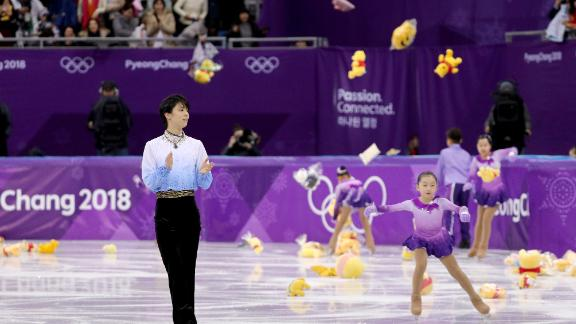 Fans throw gifts on to the ice and hold Japanese flags for Yuzuru Hanyu after his routine during the men's short program at Gangneung Ice Arena.