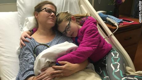 Melissa Murphy, 40, hugging her daughter Brenna while hospitalized at Mercy Hospital in Des Moines, Iowa following her heart attack in 2016.
