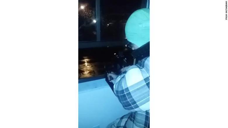 A screenshot from a video showing Nikolas Cruz firing a gun out of a window.